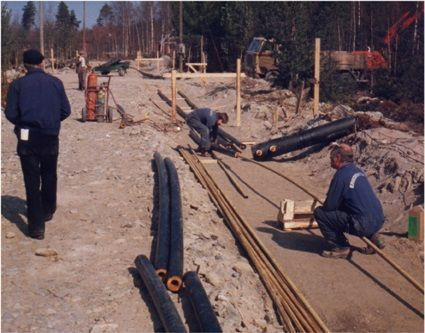 Monta ahkeraa työläistä asentamassa kaukolämpöputkia 90-luvulla